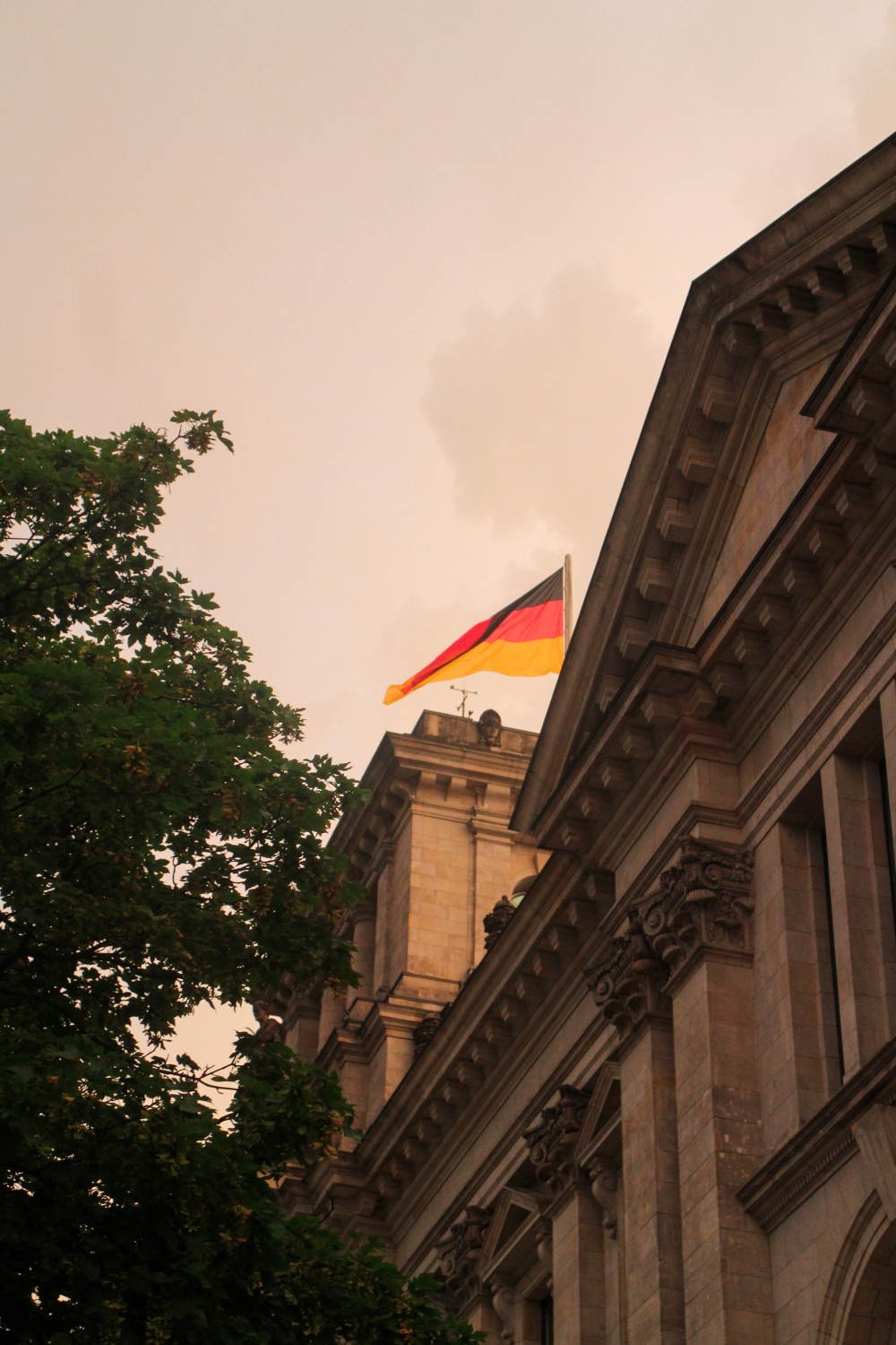 The Reichstag Building in Berlin with a German flag on top set against a pink sunset sky
