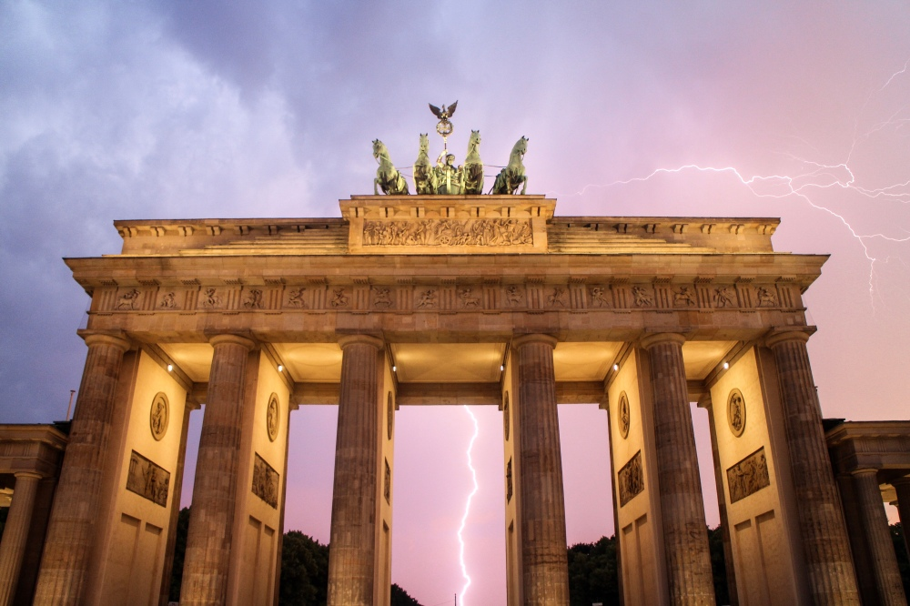 The Brandenburg Gate in the set against the evening sunset with lightning in the background.