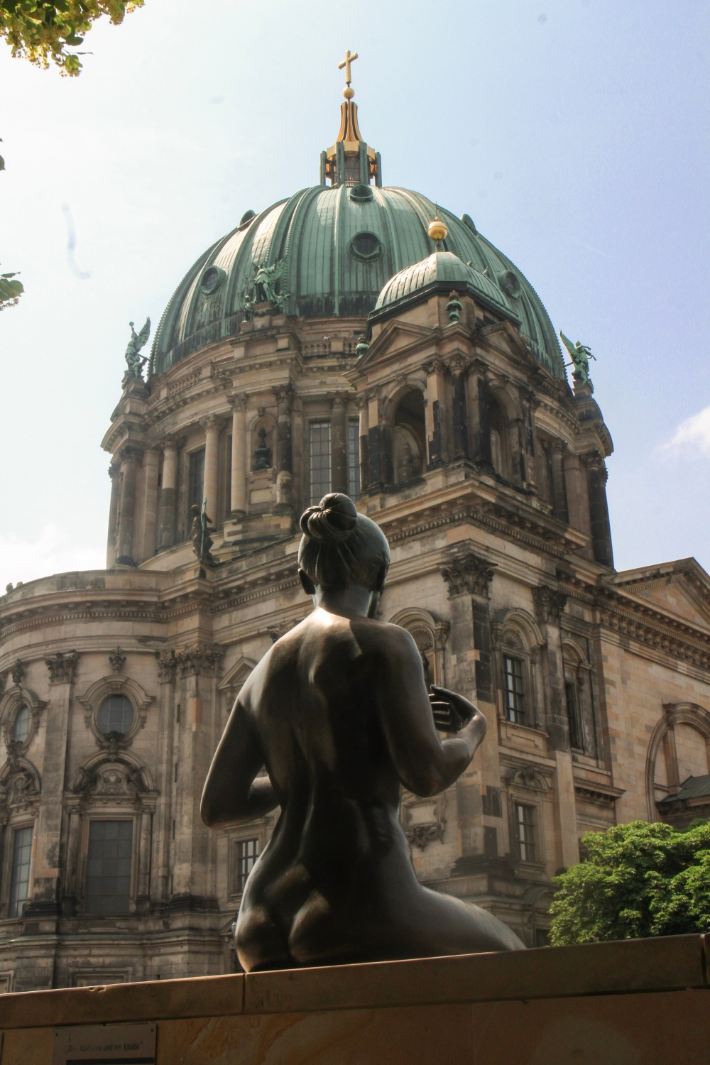 A statue of a girl looking aross the River Spree at the Berlin Cathedral