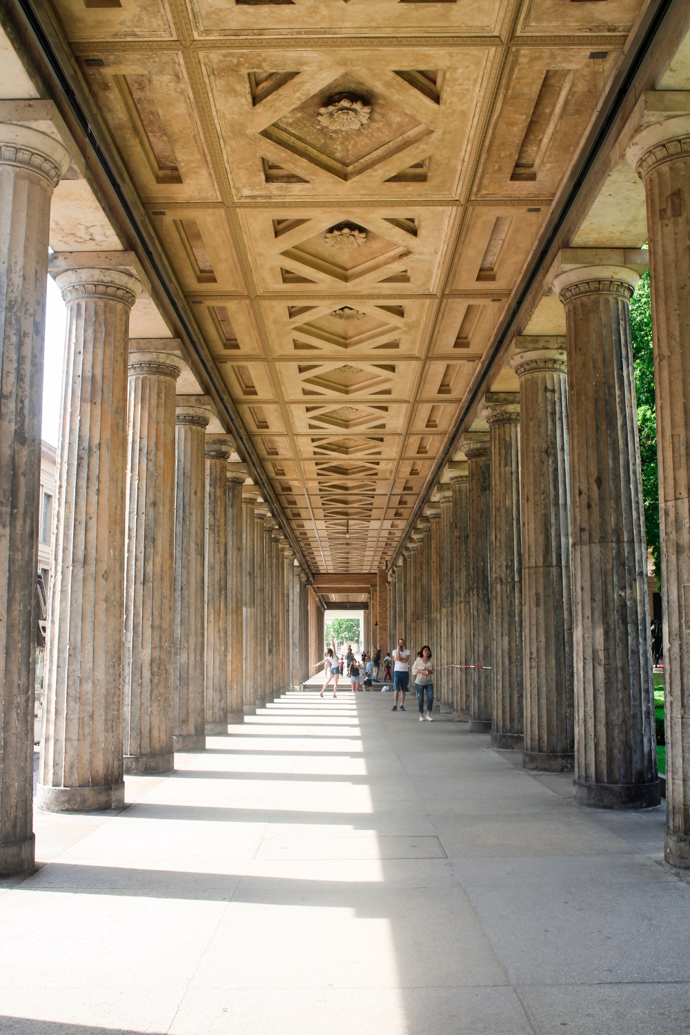 a stone walkway with pillars and a decorative ceiling