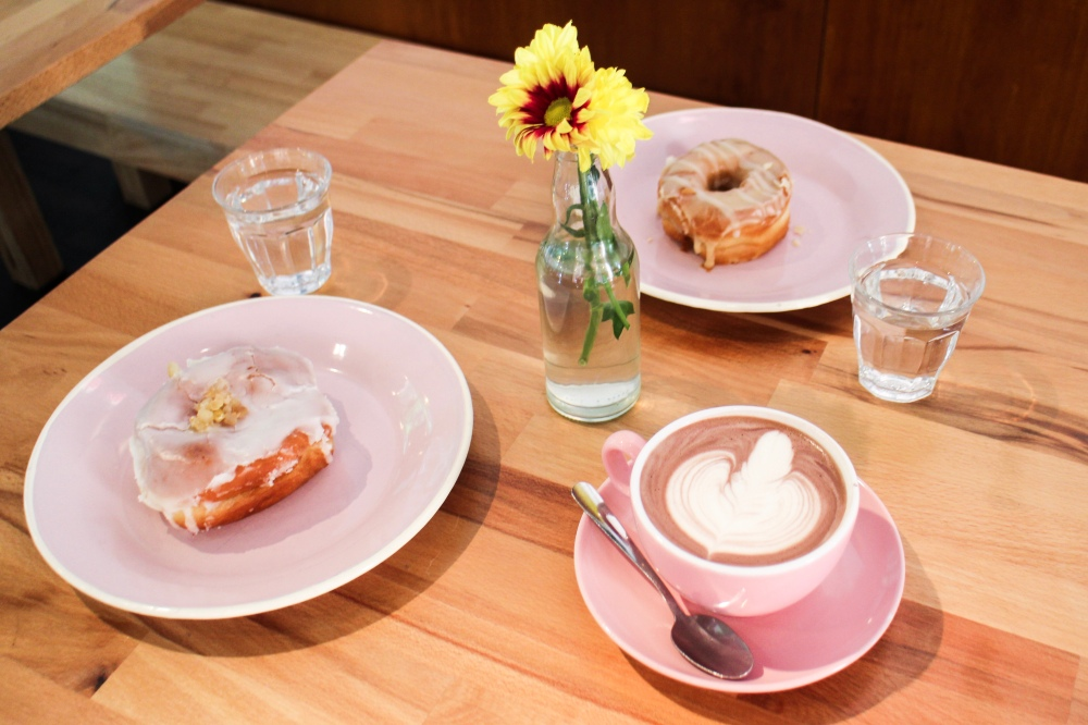 A flatlay consisting of an oat hot chocolate, a G&T doughnut, a lemon & earl grey doughnut and a little vase of flowers.