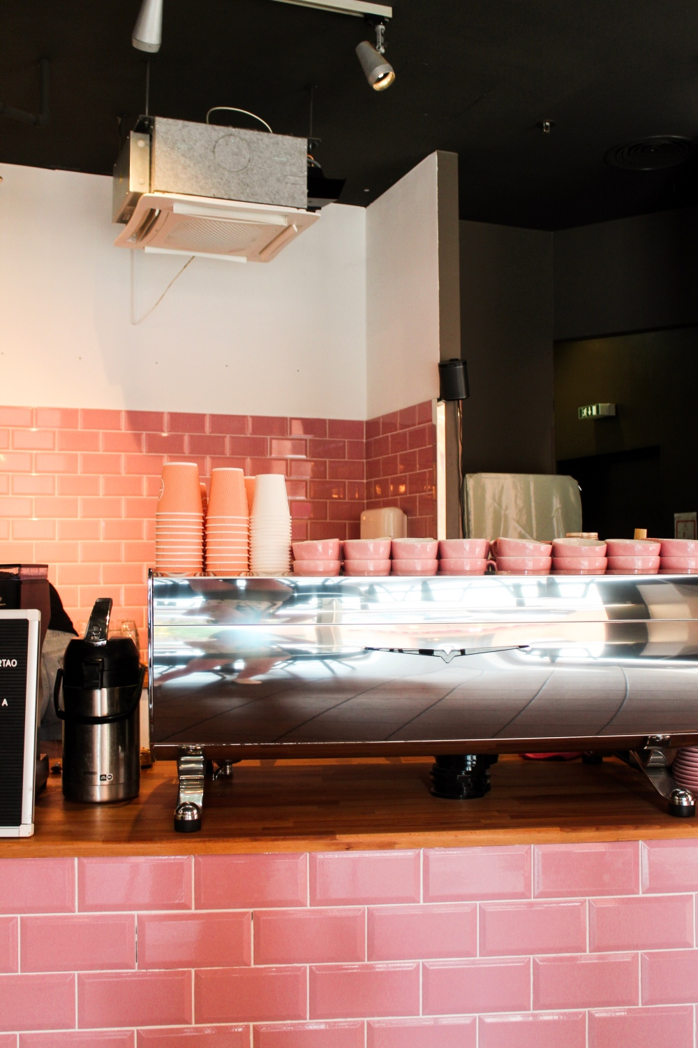 Coffee shop interior with pink tiles and pink mugs on top of the coffee machine.