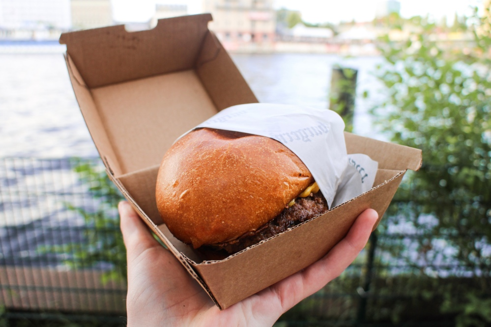 A burger in being held against the backdrop of the River Spree in Berlin