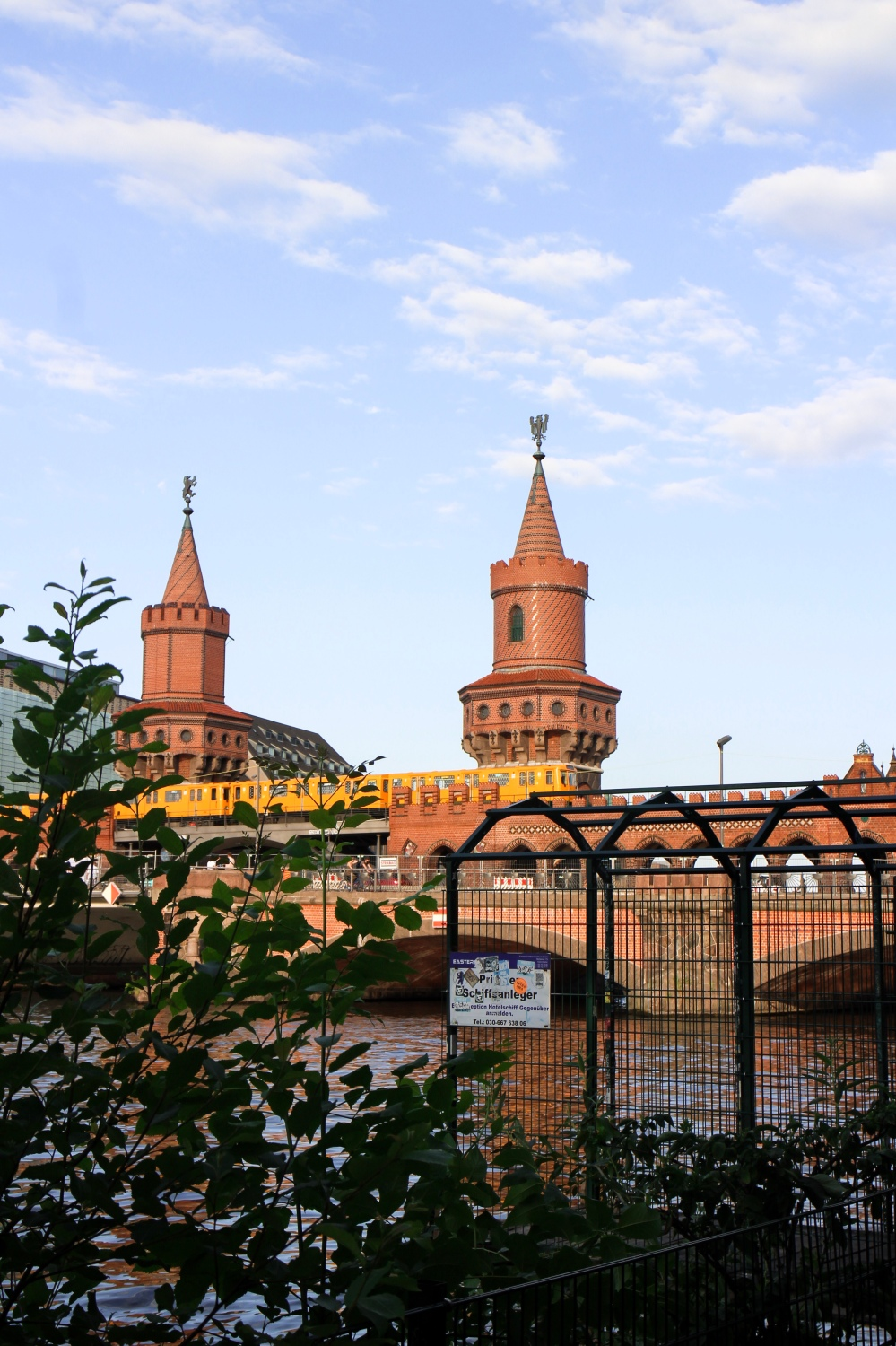 A yellow U-Bahn train going across the River Spree on a red brick turreted bridge.