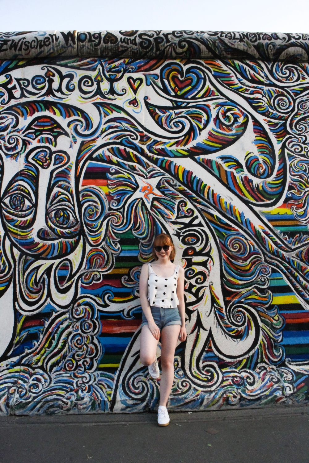 A redhead girl wearing shorts and a tank top posing for a photo against multicoloured street art.