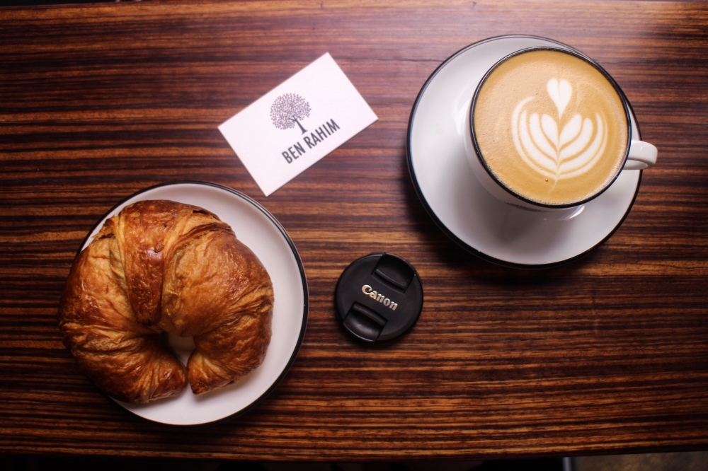 A flatlay consisting of a flat white, croissant, lens cap and a Ben Rahim business card.